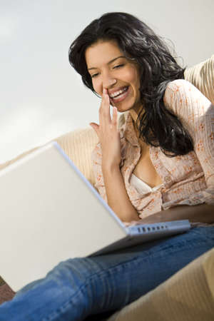 A beautiful young Hispanic woman using her laptop and laughing photo