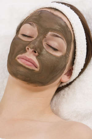 mud girl: A beautiful young brunette woman rests after having a chocolate face mask applied by a beautician  Stock Photo