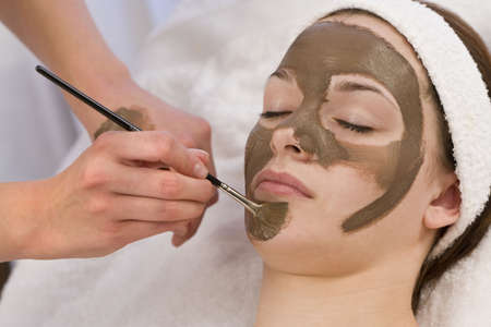 applied: A beautiful young brunette woman having a chocolate face mask applied by a beautician