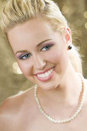 Studio shot of a beautiful young blond model with blue eyes shot against a sparkling gold background. photo