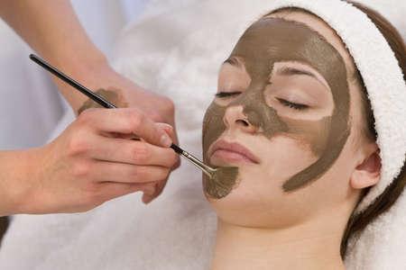 tratamiento facial: Una joven y bella mujer morena con una mascarilla de chocolate aplicado por una esteticista