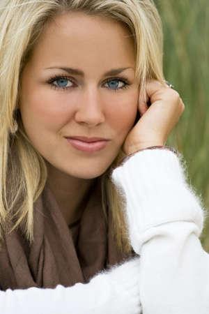 femme blonde: Une belle chevelure blonde aux yeux bleus de modèle se trouve au milieu d'herbes hautes Banque d'images
