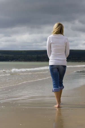 A young woman walks alone on a beach heading towards storm clouds