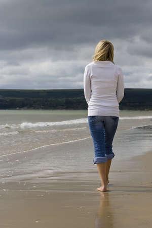 Una joven mujer camina sola en una playa en direcci�n a las nubes de tormenta  Foto de archivo