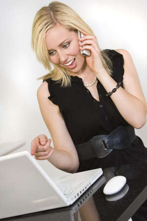 A beautiful young woman working from home on her laptop computer looks happily surprised while chatting on her mobile photo