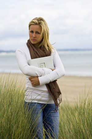clutching: A young woman walks alone on a beach clutching a book full of romantic photographs and memories