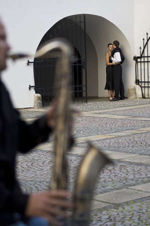A street musician playing a saxophone serenades a romantic couple as the woman looks on thoughtfully photo
