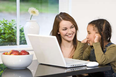 A beautiful young mother and her mixed race young daughter using a laptop at home in the kitchen. photo