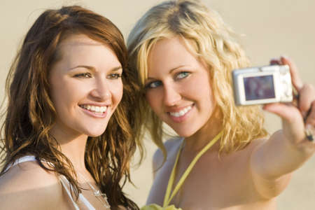 Two beautiful young women taking pictures of themselves at the beach photo