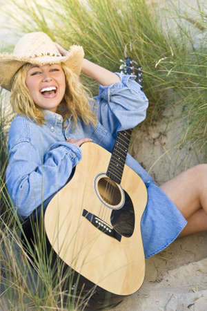 A beautiful blond young woman sitting in amongst the sand dunes and tall grass illuminated by natural late evening golden sunshine having fun playing her guitar Stock Photo