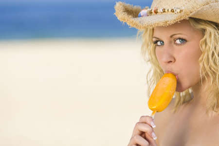 suck: A sexy and beautiful young blond woman sitting on the beach sucking an orange popsicle with golden sand and the sea behind her