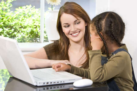 home schooling: A beautiful young mother and her mixed race young daughter using a laptop computer at home in the kitchen.