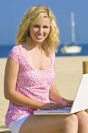 A sexy and beautiful young blond woman using her laptop on the beach with her yacht moored behind her photo