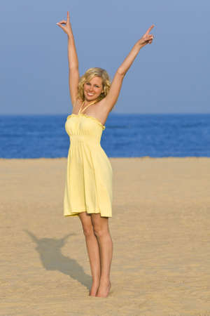 A sexy and beautiful young blond woman stretches up to a blue sky while standing barefoot on a golden beach with a deep blue sea behind her.
