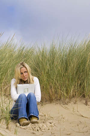 A young woman sits alone on a beach clutching a book full of romantic photographs and memories photo