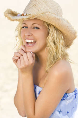 A sexy and beautiful young blond woman laughing at the beach with golden sand behind her Stock Photo