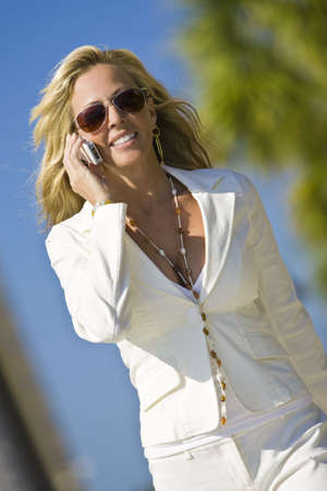 A beautiful young blond woman on the phone in a sunny location backed by palm tree Stock Photo - 3680699