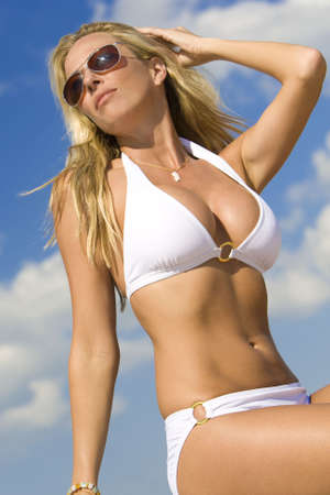 A beautiful young blond woman wearing a white bikini and sunglasses shot against a blue sky Stock Photo - 3680704