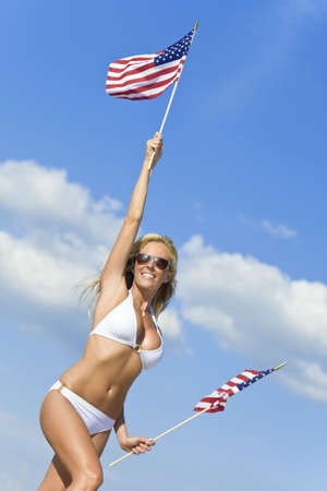 A stunningly beautiful young woman in a white bikini holds two stars and stripes flags above her head photo
