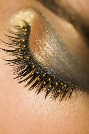 woman face close up: A macro close up of a beautiful womans made up eye with false eyelashes