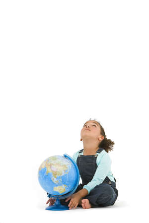 Environmental concept studio shot of a beautiful young mixed race girl with a globe looking upwards wondering what is going to happen next to planet earth photo