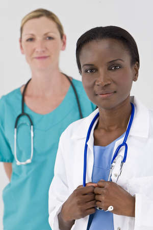 A female African American doctor with her colleague out of focus behind her Stock Photo - 3700347