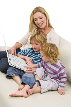 settee: A young mother and her two children using a laptop at home on a settee