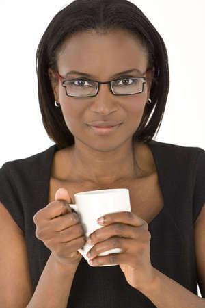 warm drink: An African American woman warming her hands around a warm drink in a white mug