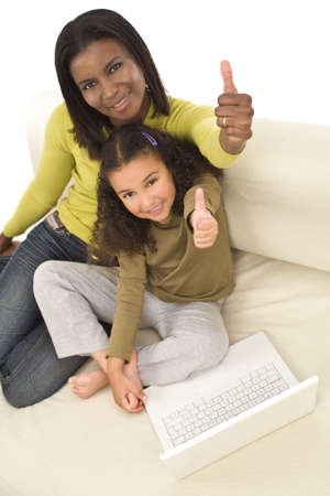 A beautiful young African American mother and her mixed race young daughter using a laptop at home and giving a thumbs up photo