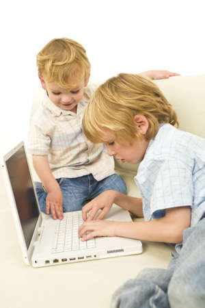 settee: Two young children using a laptop while sitting on a settee