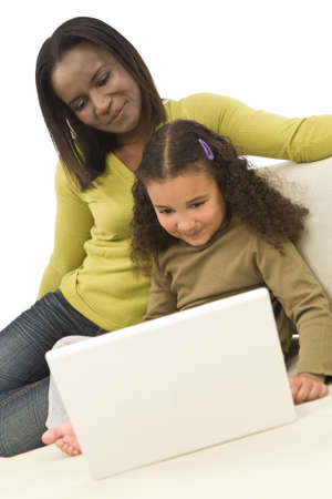 settee: A beautiful young African American mother and her mixed race young daughter using a laptop at home on a settee