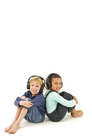 Studio shot of two children, one a blond boy the other a mixed race girl, listening to music on headphones. Isolated studio shot on a white background with a drop shadow for depth. photo