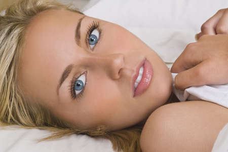 stunning: A stunningly beautiful young blond woman with piercing blue eyes lays in bed covered only in a white sheet Stock Photo