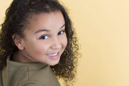 Studio shot of a beautiful young mixed race girl smiling and looking back over her shoulder Stock Photo - 3753121