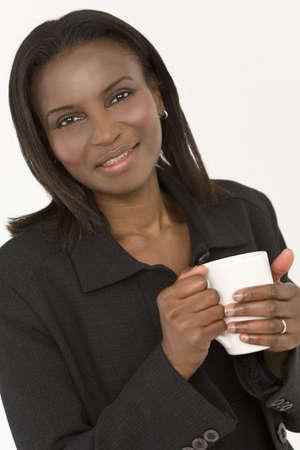 An African American vrouw opwarming haar handen rond een warme drank in een witte mok Stockfoto