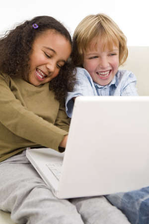 settee: Two young children having fun on a laptop computer while sitting on a settee
