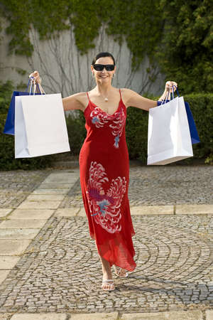 A classically beautiful woman clutching full shopping bags and looking happy photo