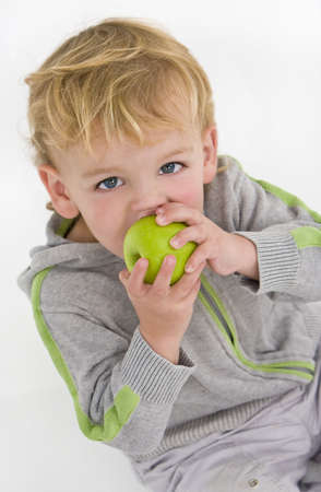A young blue eyed blond boy eating a green apple photo