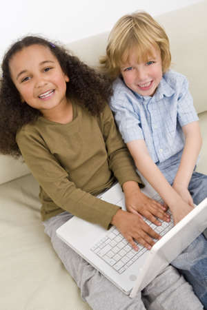 settee: Two young children having fun on a laptop while sitting on a settee Stock Photo