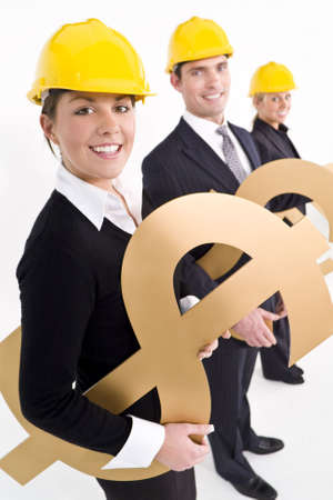 Conceptual studio shot of business executives holding various large golden currency symbols and wearing hard hats photo