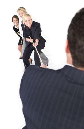 A businessman having a tug of war against three businesswomen Stock Photo - 3822980