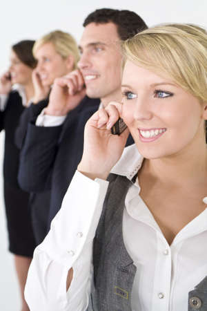 A businesswoman and a team of 2 women and a man out of focus behind her all talking on cell phones photo