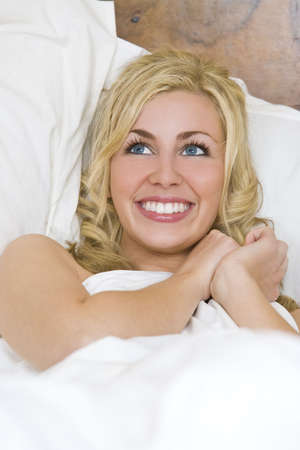 A beautiful blond haired blue eyed young woman laying sexily on her bed looking up and smiling Stock Photo