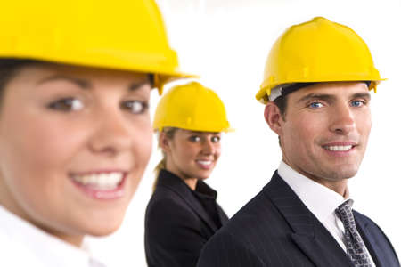 A selective focus industrial concept shot showing 2 women and a man dressed in hard hats. The focus is on the man on the right of the shot.