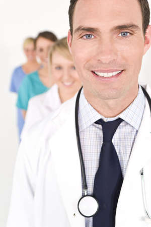 him: A male doctor with his team of colleagues out of focus behind him.