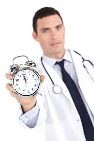 12 oclock: A male doctor holding out an alarm clock ticking ever closer to 12 oclock. The focus is on the clock face.