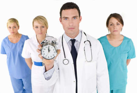 A male doctor backed by his medical team holding out an alarm clock ticking ever closer to 12 oclock. The focus is on the clock face. photo