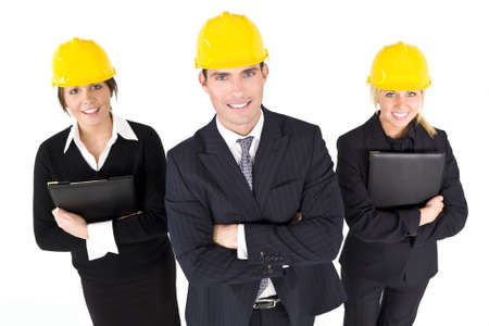 yellow helmet: An industrial concept shot showing 2 women and a man dressed in hard hats. The focus is on the man in the foreground