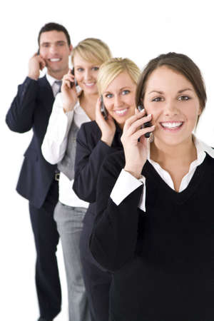 A team of one businessman and three businesswomen all talking on cell phones, the focus is on the brunette woman at the front. Stock Photo