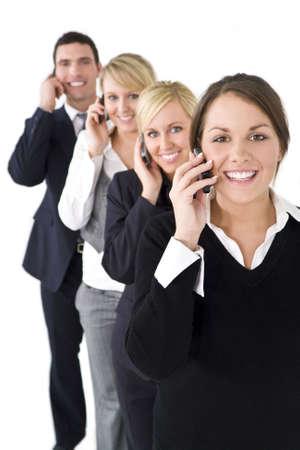 Un equipo de un empresario y tres mujeres empresarias de hablar sobre todos los tel�fonos celulares, la atenci�n se centra en la mujer morena en la parte delantera.